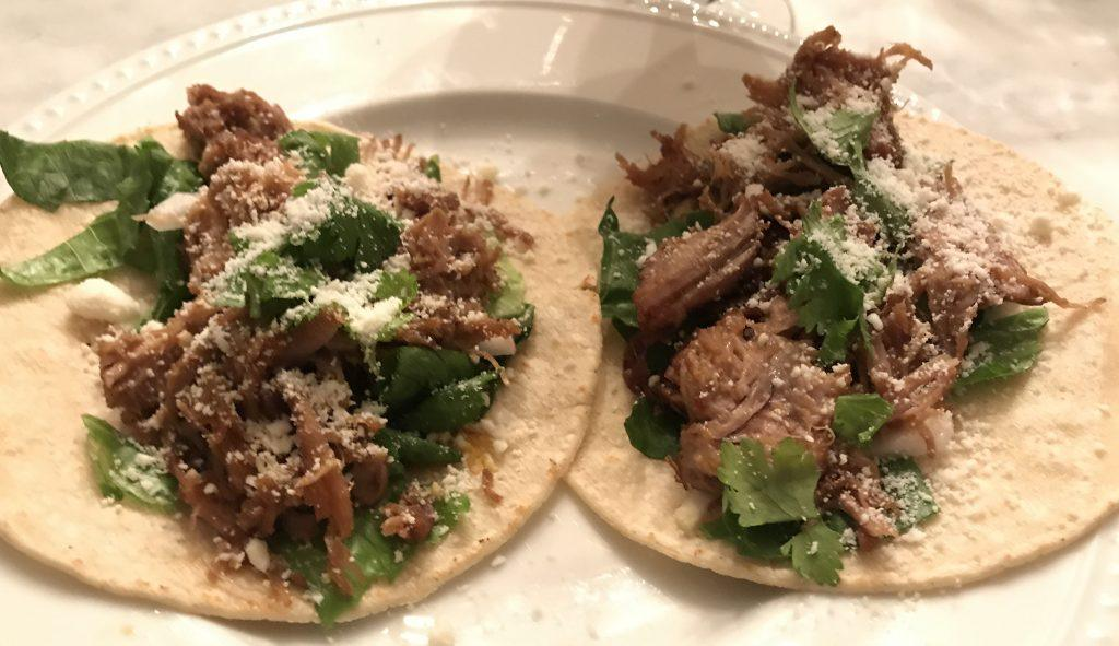 tortillas with carnitas, lettuce, cotija cheese and salsa verde