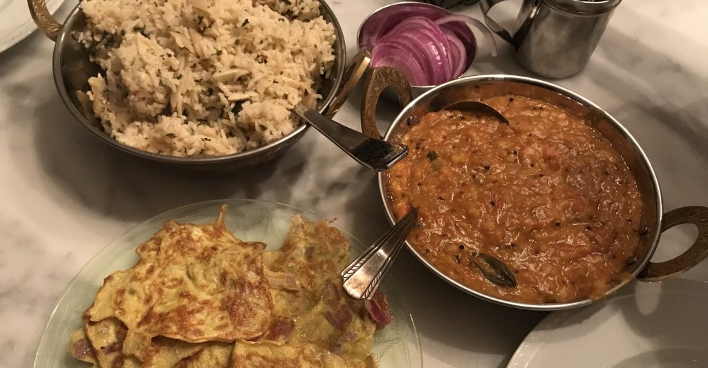 an indian homecooking feastdal, indian omelet and pulau, with sliced red onions