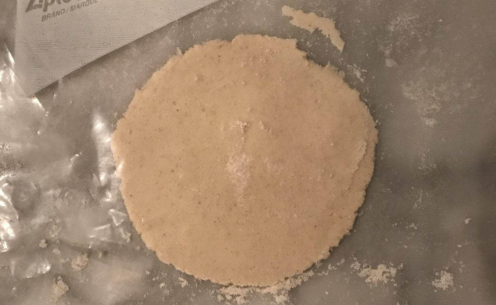 nice round home made tortilla, flattened by a plastic-covered cookbook