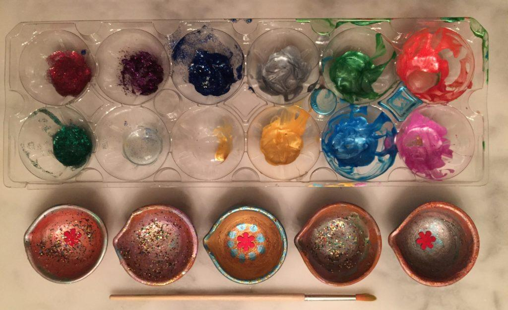 5 home-painted diyas and the egg cartons with leftover paint