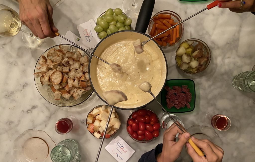 top view of diners dipping baguette into a pot of fondue and all the proper dipping items. and french red wine.