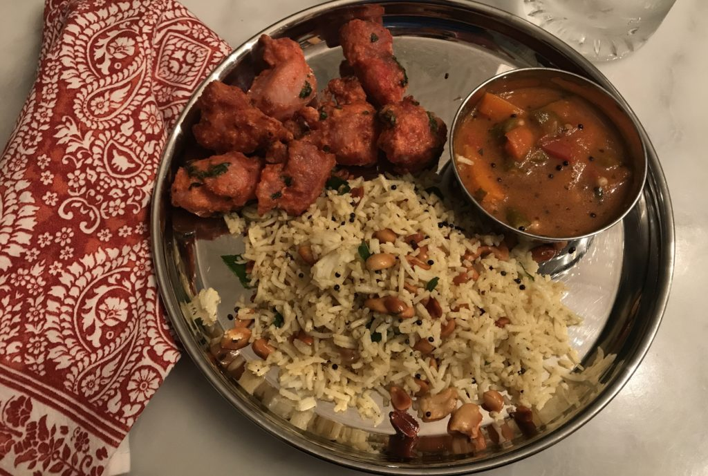chicken 65, lemon rice and sambhar on a traditional indian steel plate