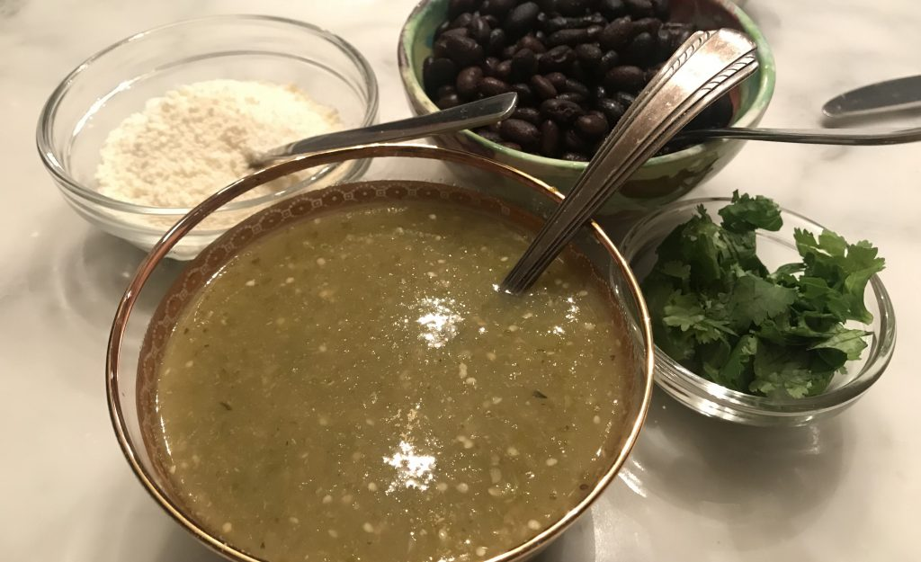 salsa verde, cotija cheese, cilantto and black beans ready for carnitas tacos