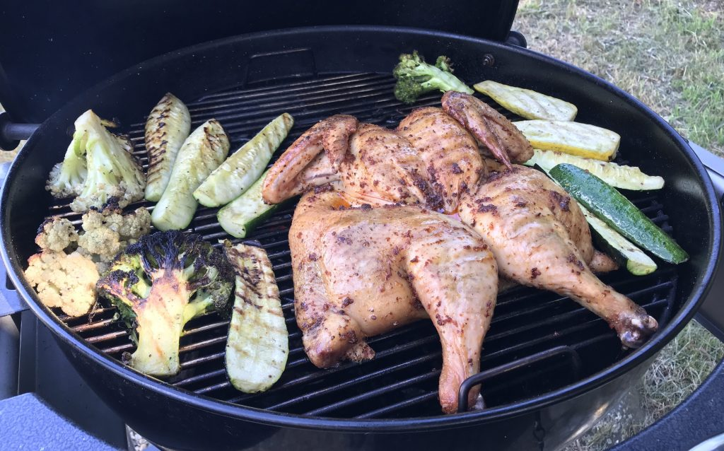 stpatchcocked chicken on the grill with seasonal veggies roasting