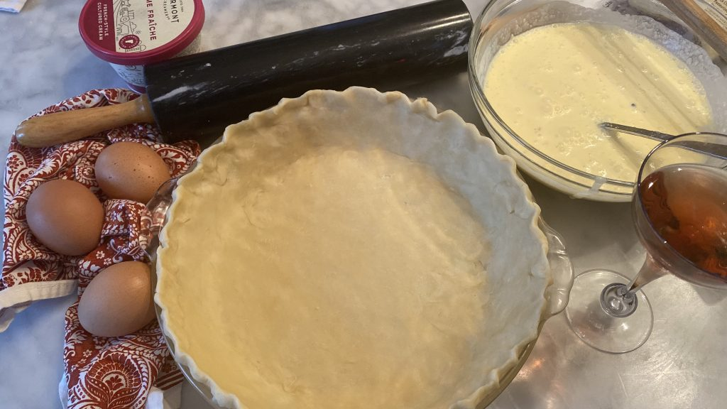 fresh homemade tart crust for a quiche, pressed into pie plan and ready for a pre-bake, along side the prepared custard to bake into quiche.