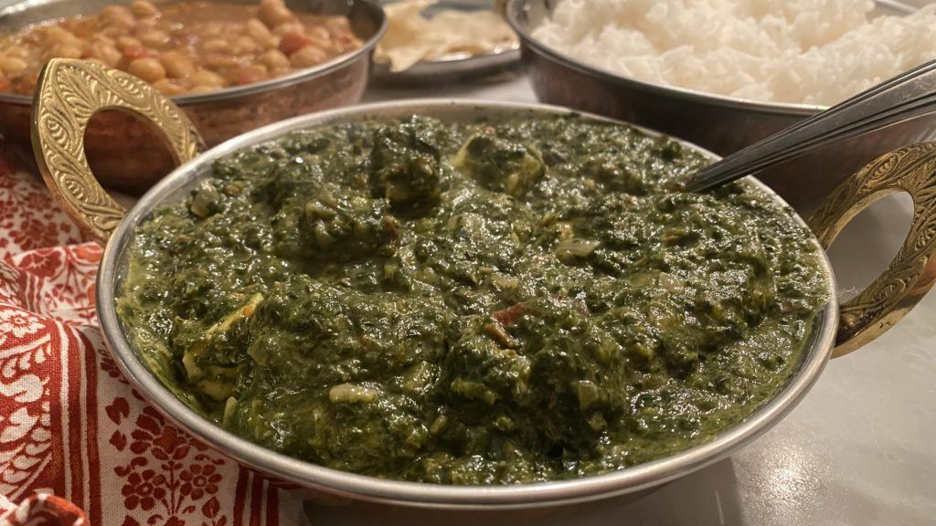 saag paneer in a copper serving bowl with rice behind it