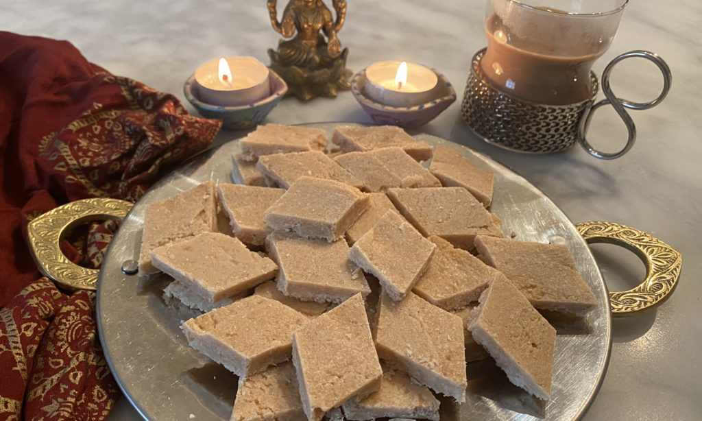 coconut burfi on a traditional indian tray with candles and laxmi