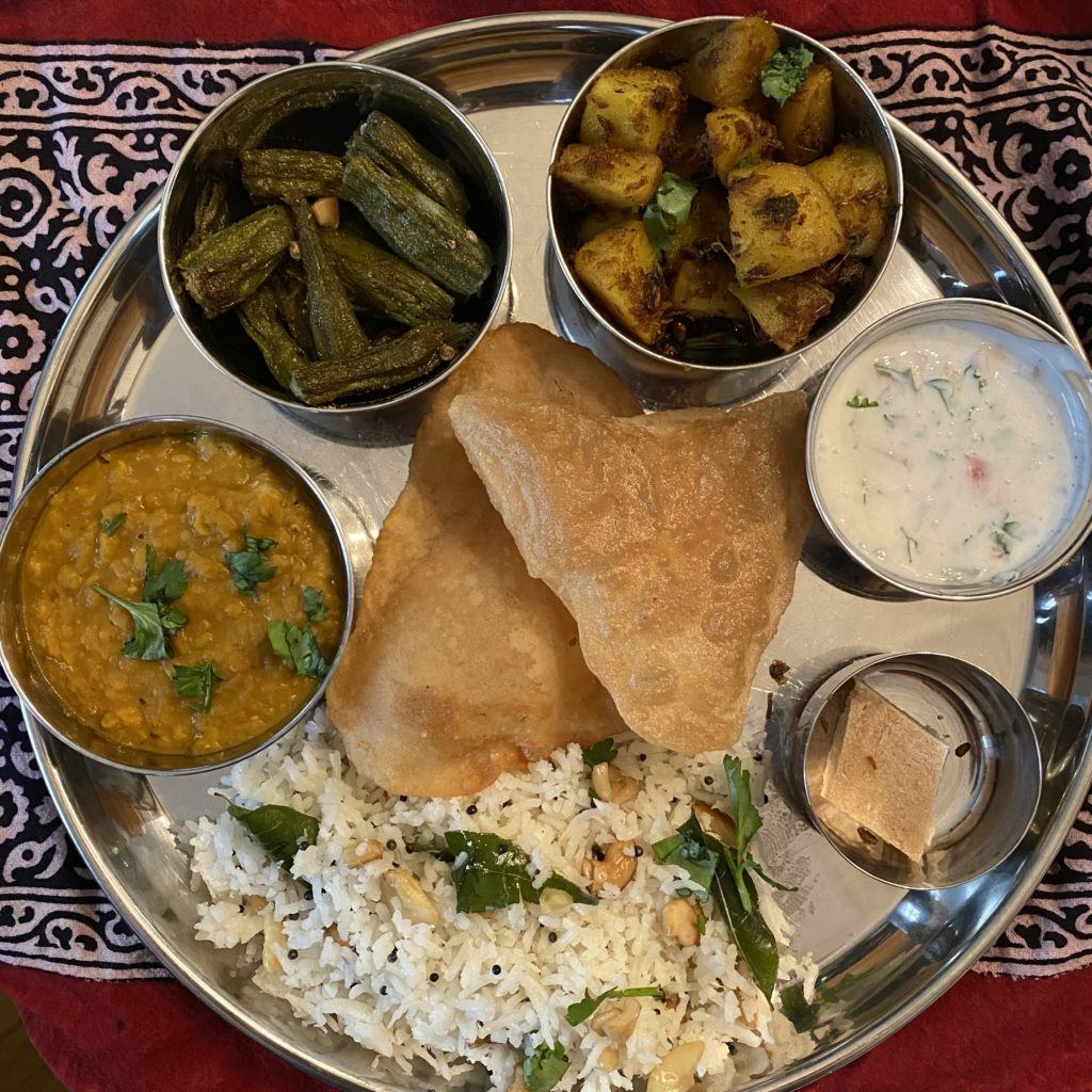 clockwise from bottom: coconut ghee rice, coconut dal, chaat okra fries, jeera aloo, raita, coconut burfi and in the center, nani's puris.