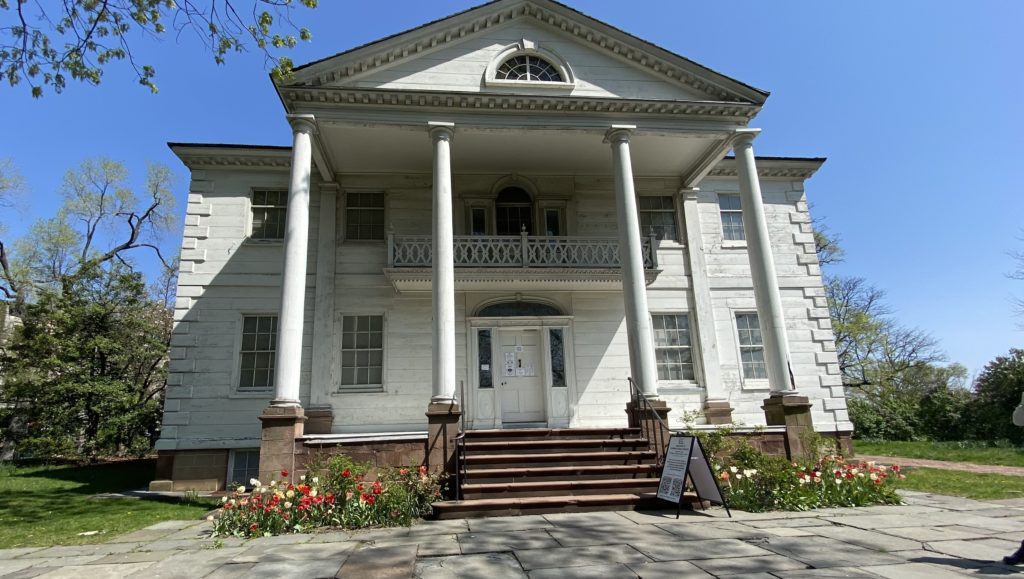 the front of the morris-jumel mansion on a sunny spring day