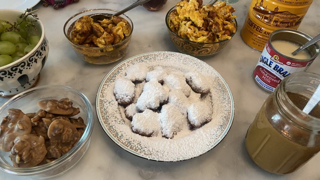homemade brunch feast for festing in place april 2021. classic beignets, crawfish beignets, red beans and rice with fried egg, cold brew coffee and crawfish scrambled eggs